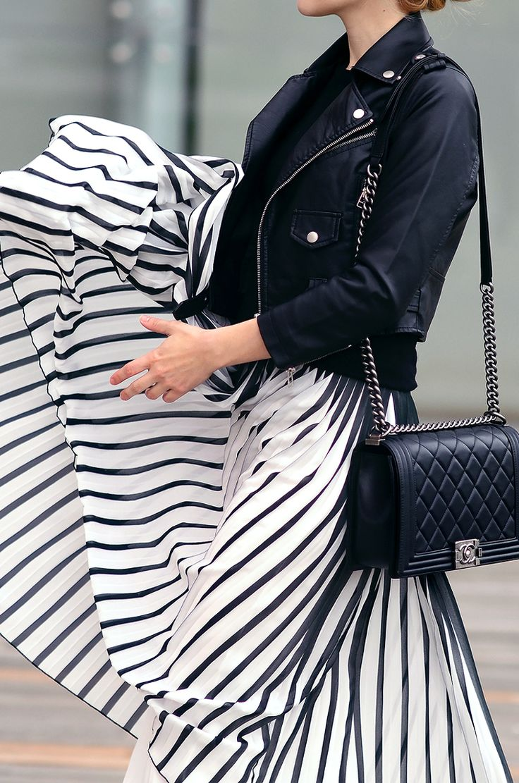 Great contrast of feminine striped skirt and tough jacket.