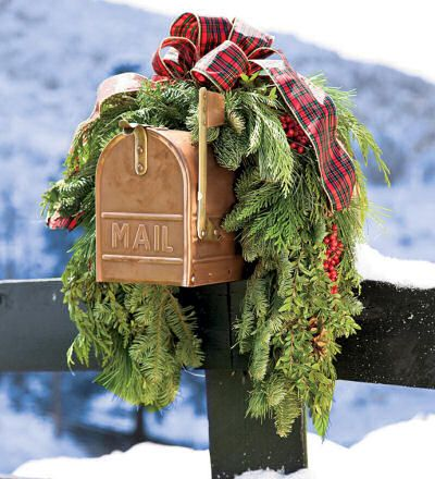 A rustic garland with faux holly berries and big red plaid bow decorates this tan colored mail box beautifully.