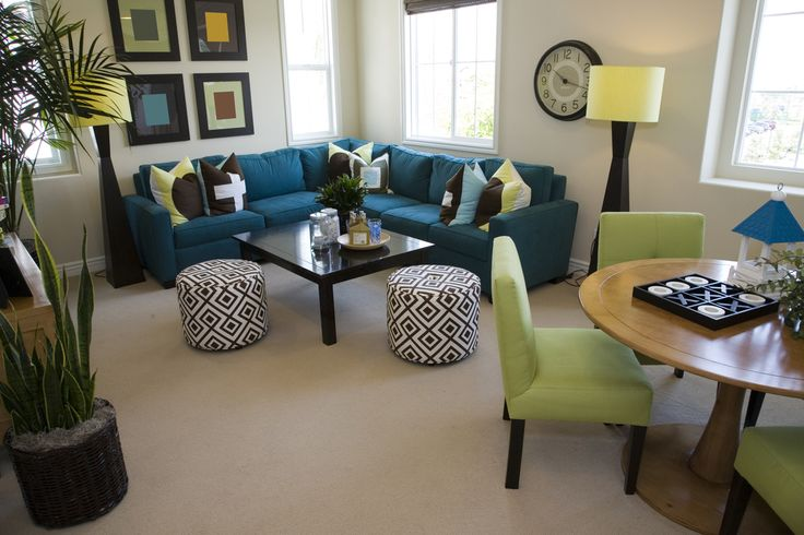 Great example of creating a great living room in a small space.  Living room is part of an open concept living area and is comprised of a blue L-shaped sectional, one simple dark coffee table and two cylinder dark brown and white cushioned stools.