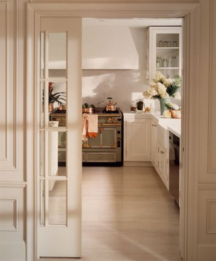beveled glass pocket doors open a traditional paneled dining room onto a gleaming modern kitchen that