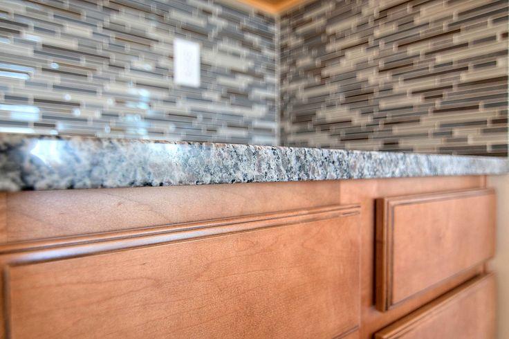 Amazing workmanship on this Ebb & Flow, Dusk & Dawn 1x2 linear set backsplash! Also pictured- Caledonia Slab Granite, Palomino Manchester Maple cabinets. https://cbhhomes.com