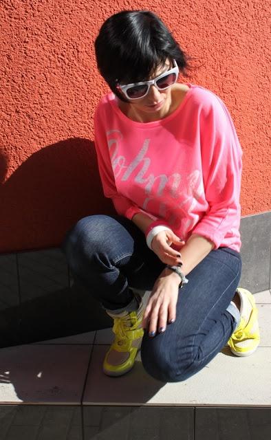 białe okulary przeciwsłoneczne, neonowa różowa bluzka, ciemne jeansy, neonowe sportowe buty DeeZee