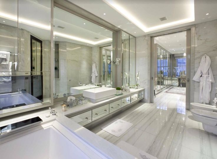 Mirrors, stone and lighting effects enhance this large bathroom to the height of luxury.  Photo credit- Wolff Architects, UK
