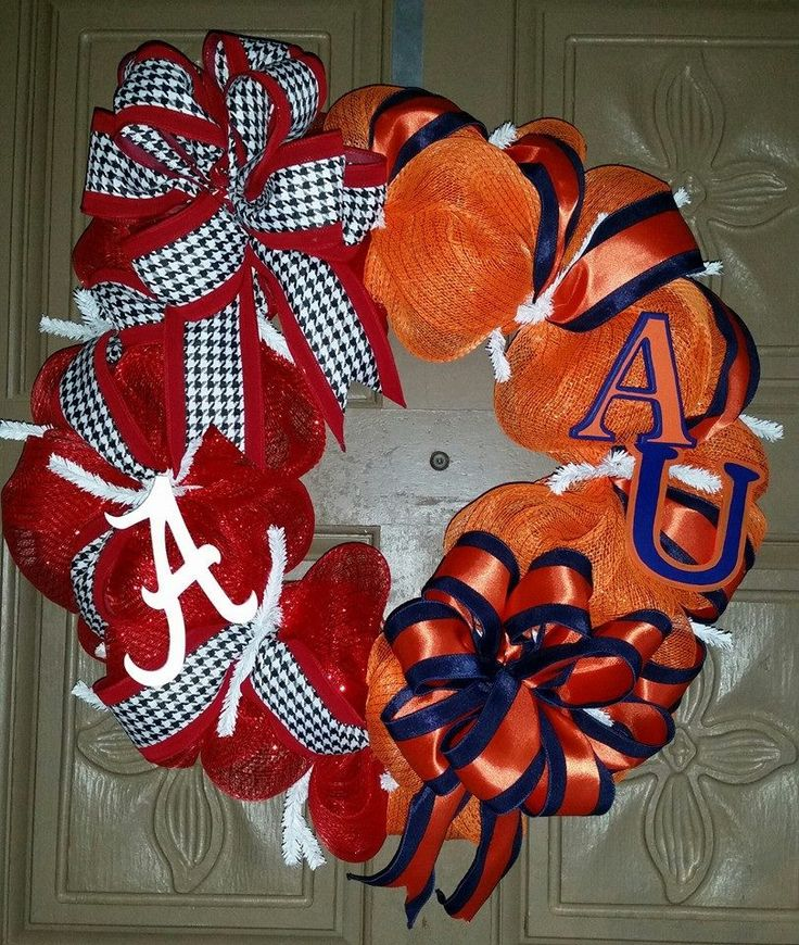 """This is a 24"""" hand crafted Alabama/Auburn house divided deco mesh wreath. One side is made of orange, blue and white mesh with orange and blue accenting ribbon and a hand painted A and U letters. The"""