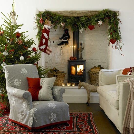 A garland hangs over the fireplace with Scandi-chic decorations to create a warm and cosy Christmas feel in this living room.