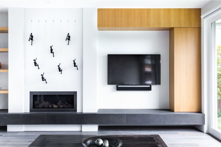 A clever, modern living room with hidden cupboards in the natural wood around the wall-mounted television and a set of climbing men displayed above the enclosed fireplace. Designed by http://www.canny.com.au/