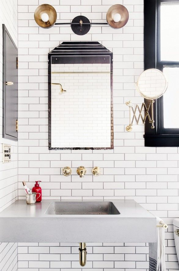 Subway tile in black and white bathroom with industrial lighting and gold accents