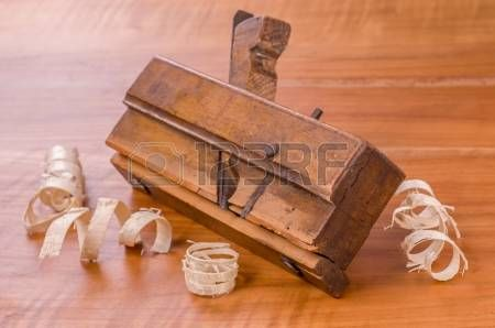 old molding plane with shavings on a cherry wood board
