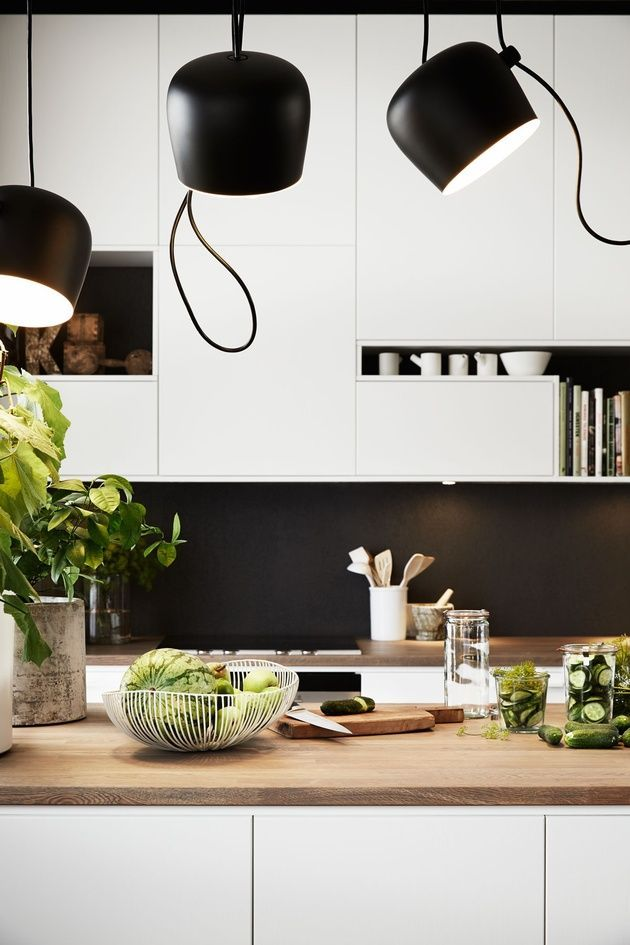 AIM pendant lighting casts a bright glow in this kitchen featuring white cabinets and wood counter tops.