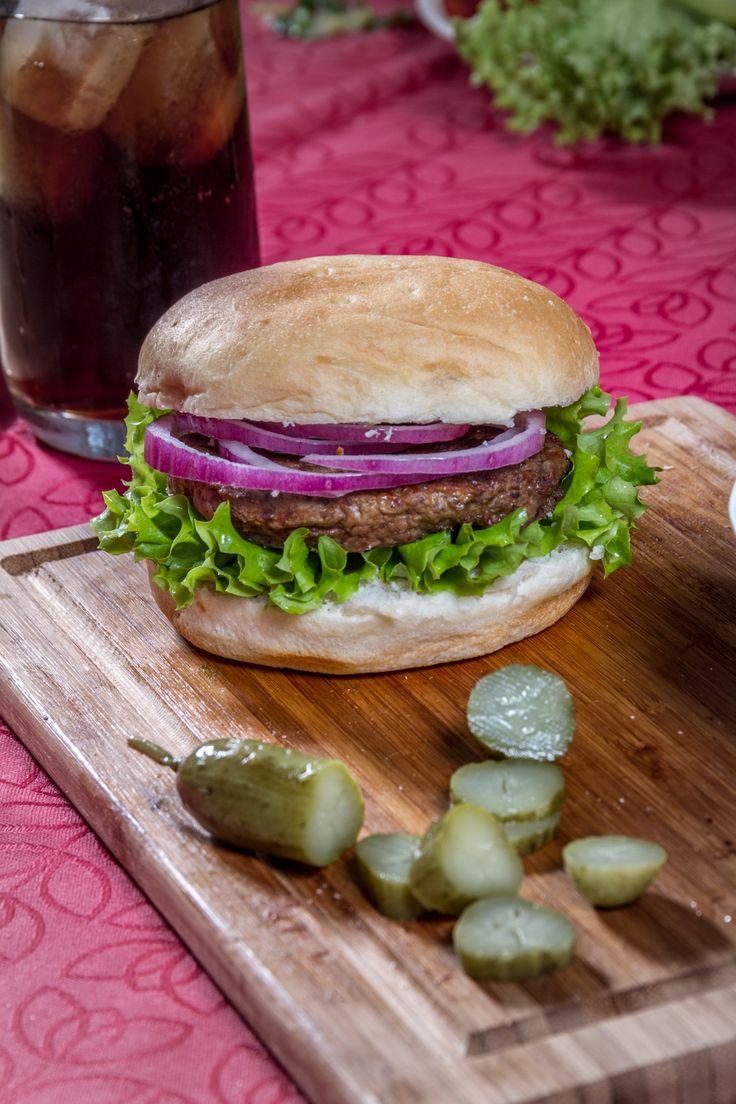Prepara un exquisito sándwich para un picnic increíble. Pepinillos, cebolla morada, lechuga y una hamburguesa casera. ¡Maravilloso!
