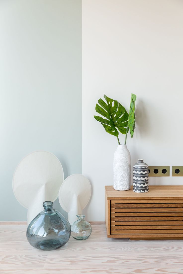 Wall paint detail half pale green, half off white in modern apartment designed by Studio Mills.