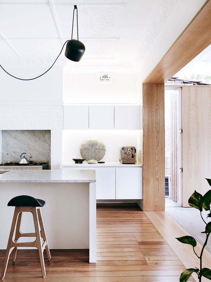 """In the kitchen, shields and bowls the couple bought in Africa are earthy elements in the restrained palette. **Benchtop** and **splashback** in Carrara marble are from [Milestone Building](http://mbuilding.houzz.com.au/?utm_campaign=supplier/
