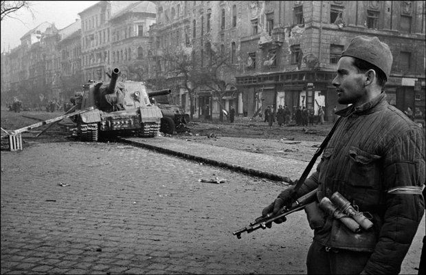BUDAPEST, Hungary—A Hungarian solder, whose armband indicates that he has joined the insurgents, stands in front of a disabled Soviet tank, 1956.
