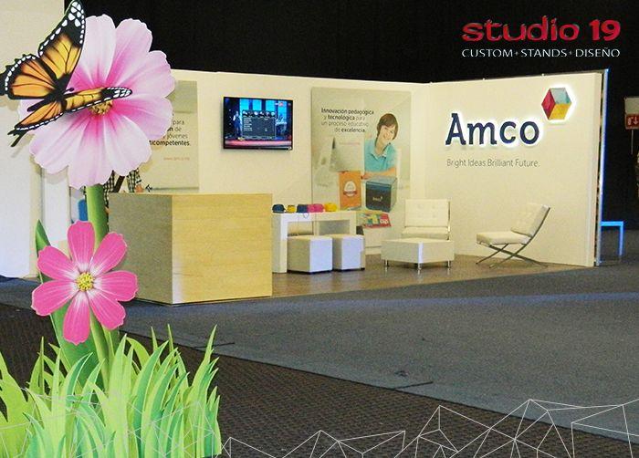 Diseño de stand 'AMCO' montado en custom. Logotipo realzado con iluminación led por la parte posterior. Decorado con barra de madera y como mobiliario una sala Barcelona, una mesa de trabajo con Puff´s