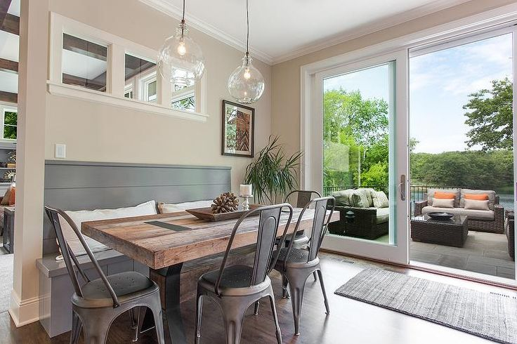 Industrial style dining room features a built in gray shiplap dining bench facing a salvaged wood x based dining table lined with Tolix Chairs illuminated by clear glass pendants.