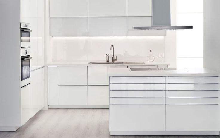 Modern white IKEA kitchen with white worktops and stainless steel appliances