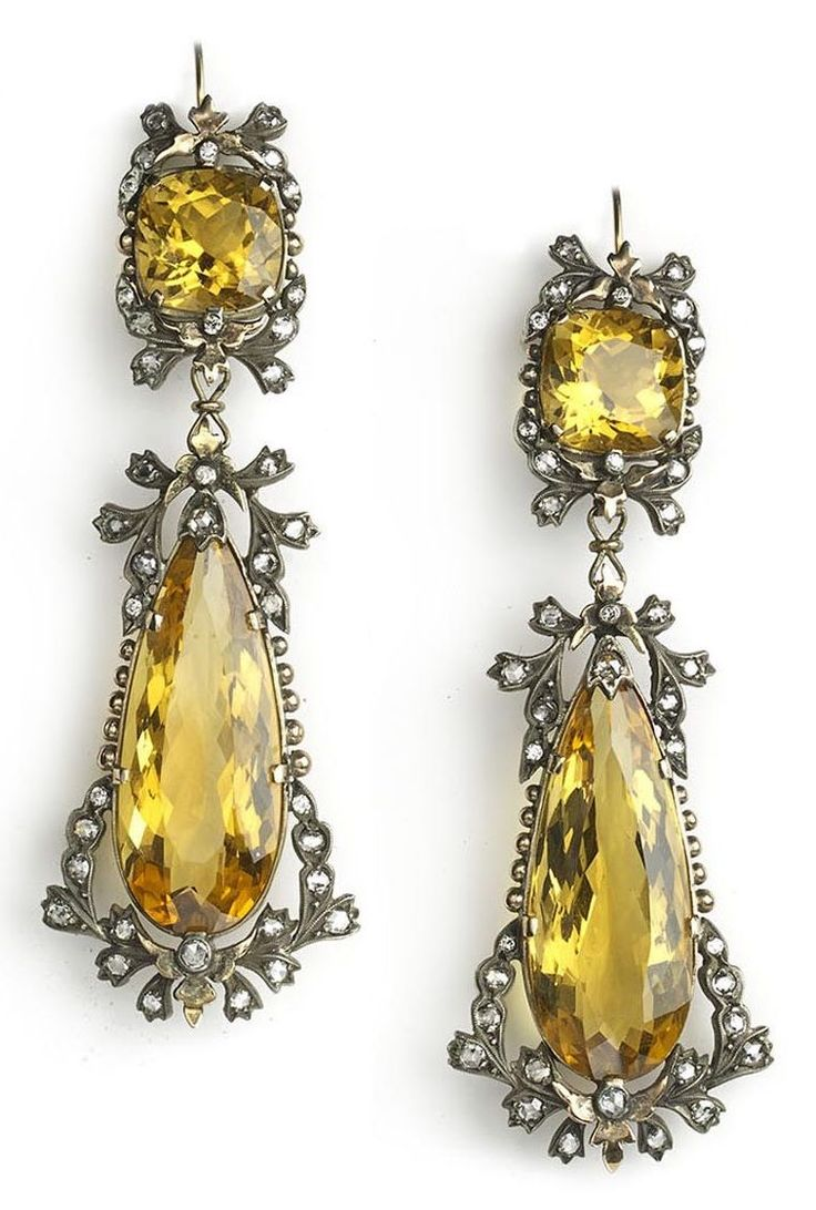 A pair of fine antique diamond and citrine drop earrings, circa 1880. Each earring set with a cushion and pear shape citrine within a bow and swag old-cut diamond surround, mounted in silver on gold. #antique #earrings