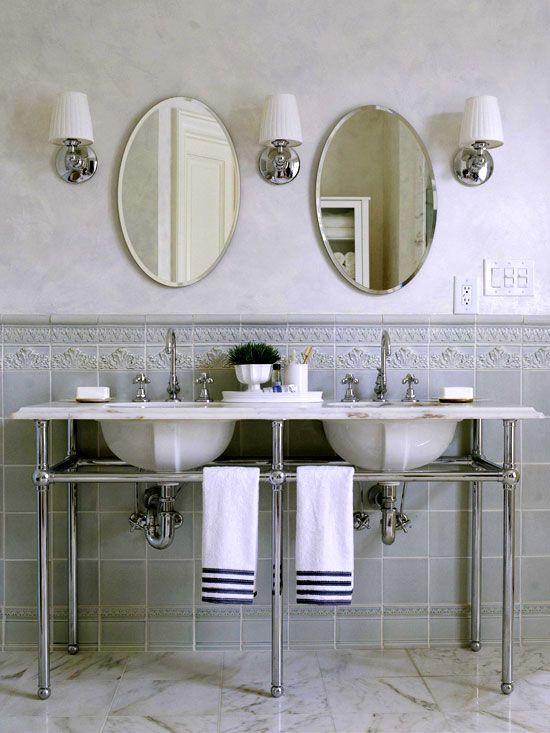 Soft blue-gray tile wainscoting topped with a simple border tile adorns these bathroom walls. The tiles provide a backdrop for the double-sink vanity, which is constructed from a single piece of white marble.