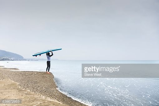 Young athletic man standing on the beach holding a Stand Up Paddleboard looking at a calm ocean