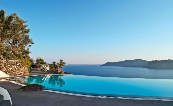 Infinity swimming pool overlooking the ocean with palm trees
