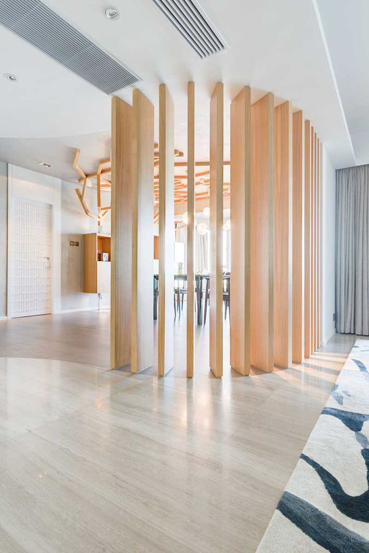 15 Creative Ideas For Room Dividers // This contemporary apartment has lot of elements of nature throughout it, including the wooden space divider between the dining and living areas.