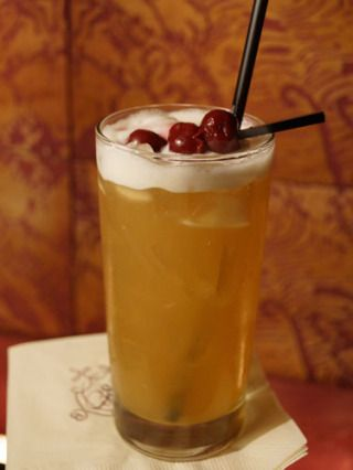 1½ oz. Woodford Bourbon  ½ oz. Lime Juice  Ginger ale  3 pineapple chunks  Garnish: cherry  Muddle pineapple chunks in a cocktail sha...