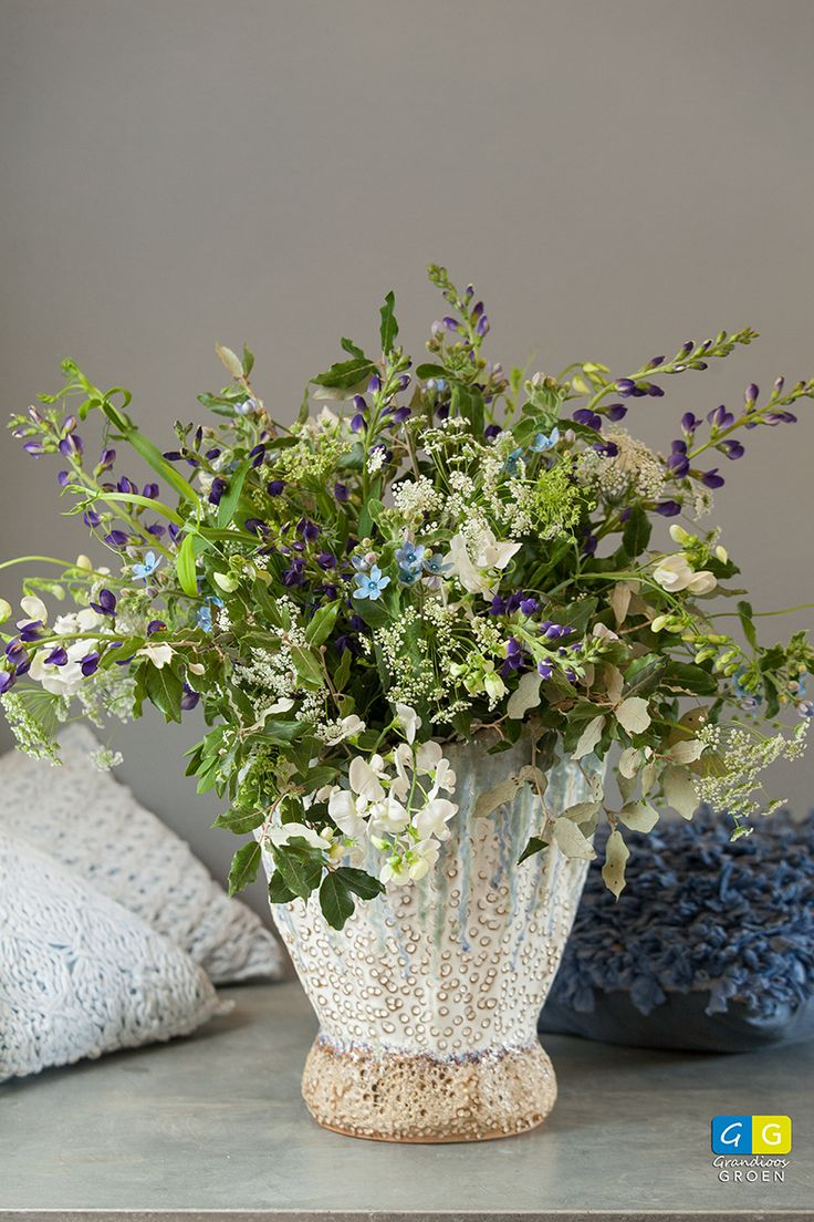 Een veldboeket met voornamelijk witte en blauwe kleine bloemen geschikt in een vaas die er uitstekend bij past.