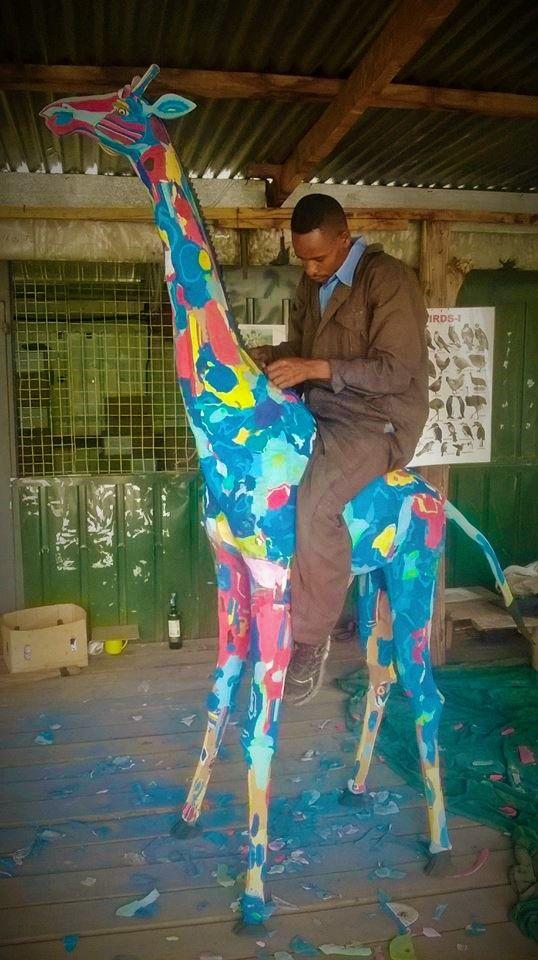 riding a life size flip flop giraffe
