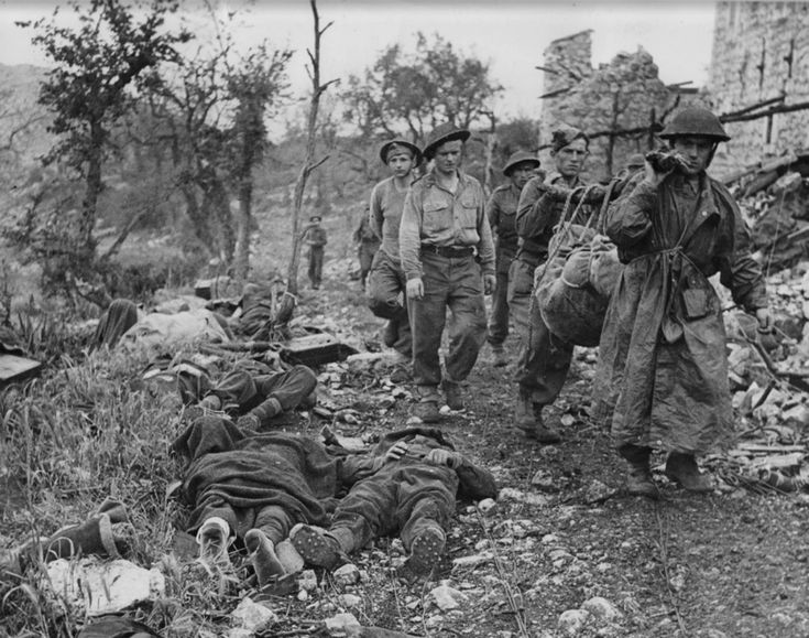 Allied Polish soldiers carry a dead comrade from the rubble of Monte Cassino shortly after the fall of the abbey during the Battle of Monte Cassino. Dead German defenders, including one stripped of his hobnail boots lie along the path. The Battle of Monte Cassino was a costly series of four assaults by the Allies (including, American, Polish, Free French, British, Canadian, Indian, Algerian, Moroccan, New Zealand, Nepali, South African and Italian Royalist troops, amongst others) against…