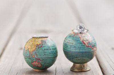 Wedding photography - Rings resting of mini globes of the world map.