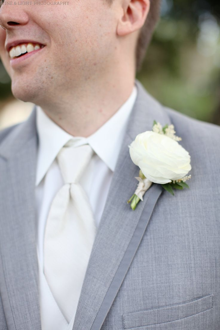 the groom wears a boutonnière of white ranunculus and white astilbe on the lapel of his grey suit.