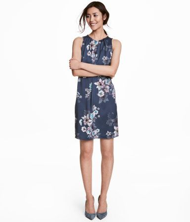 Dark blue/floral. Sleeveless dress in satin with a printed pattern. Pleats at front of neckline. V-neck at back with horizontal strap across top. Unlined.