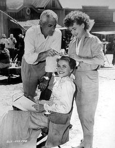 Jeff Chandler kibitzes while Dolores Hart's mother, Harriett, fixes her hair between scenes of The Plunderers