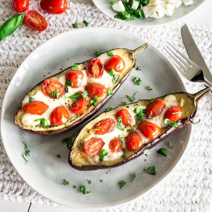Fruchtige Kirschtomaten und Mozzarella haben es sich im warmen Fruchtfleisch der Aubergine bequem gemacht.
