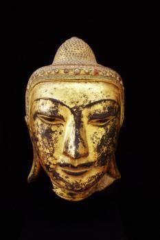 Tête de Bouddha au doux sourire surmontée de l'ushnisha avec un décor frontal de petite verroterie polychrome. Laque sec, partiellement doré. Birmanie Royaume d'Amarapura fin XVIIIeme. Ht: 23 cm.