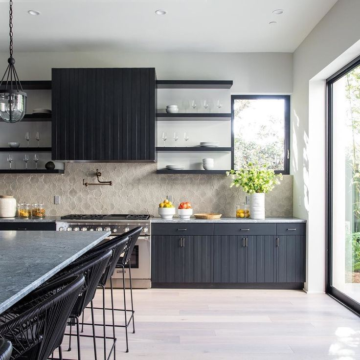 This black kitchen is the kitchen of my dreams and the kitchen I want to wake up and make coffee in every single morning! The way the black cabinetry and elemetns go with The neutral materials for floor and blacksplash and the way it opens up completely to the outside is JUST PERFECTION! photo by bethanynauert