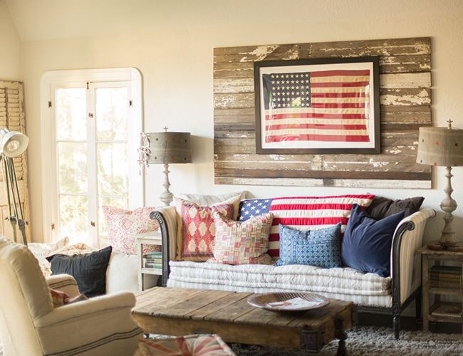 A neutral color scheme and rustic pallet backdrop make the framed American flag hanging in this living room even more of a focal point.