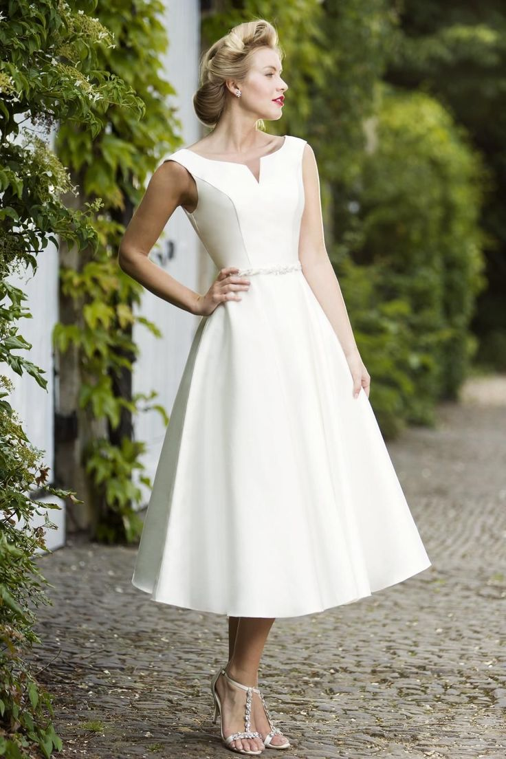 This chic Mikado tea length wedding dress with bateau neckline, is pure elegance. Its retro swing skirt and simple detailing at the waist says understated glamour. Pair this gown with stylish heels for a statement, vintage-inspired bridal look. Mikado covered buttons over zip closure.