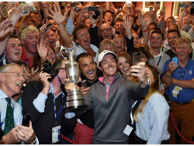 Rory McIlroy of Northern Ireland takes a selfie with the Claret Jug and members of Royal Liverpool in the clubhouse after his two-stroke vic...