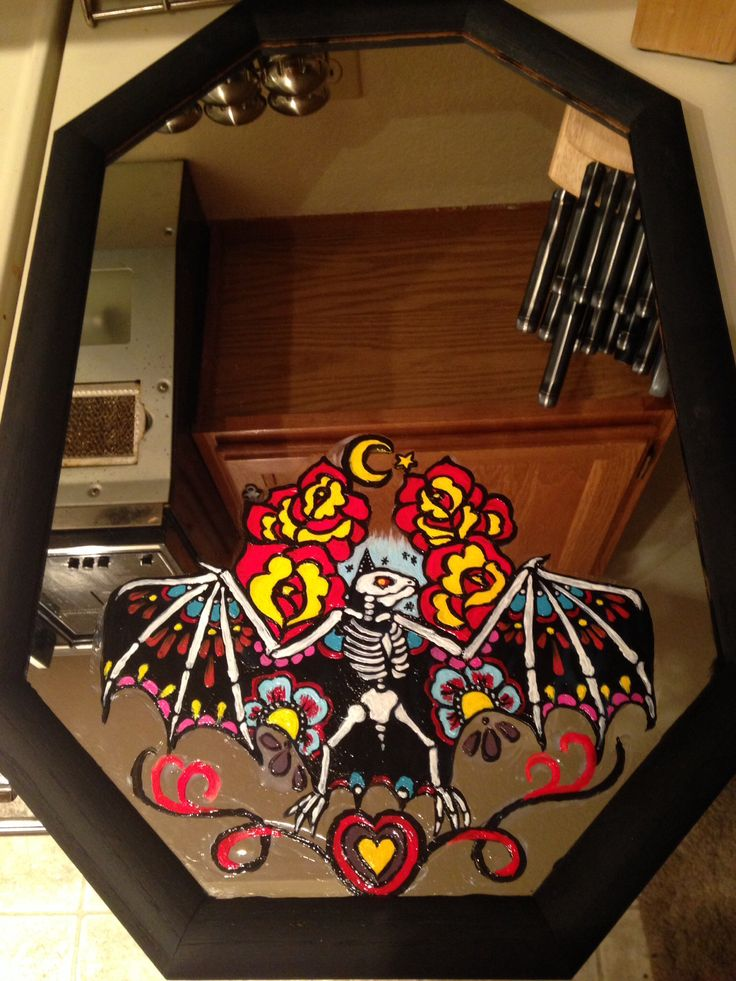 $2 thrift store frame. I painted it chalk black then painted a day of the dead bat on it!