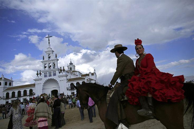 A pilgrim couple rides a horse next to the shrine of El Rocio.