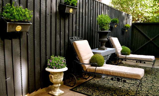 Beaux Mondes Designs - small area, black painted fence with planter boxes with boxwood and other greenery.