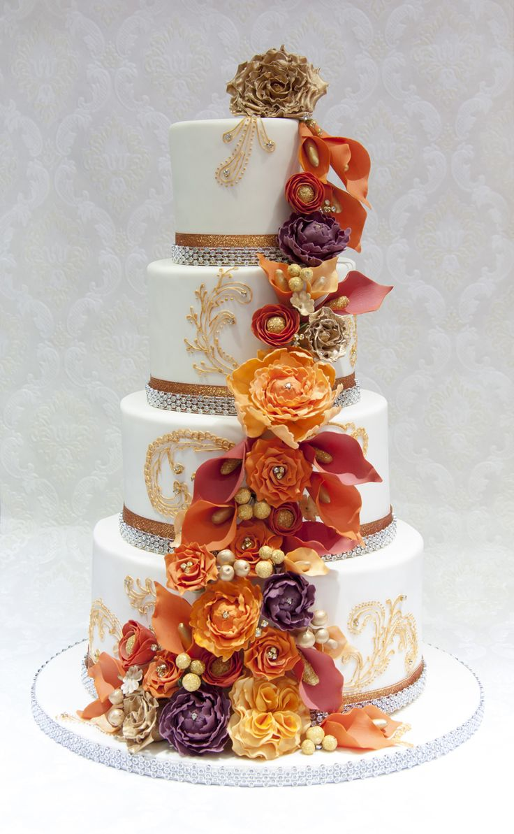 This orange and gold cake was for an Indian wedding, with emphasis on gold and bling. With lots of sparkle, there is trim around the base of each tier and diamantes at the centre of certain flowers. Handpiped and hand-painted the mehndi patterns are featured. By Cherry Blossom Cakes. For more inspiration visit www.weddingsite.co.uk