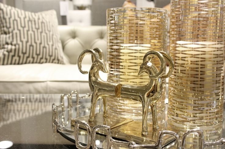 http://www.avenuedesigncanada.com gold book ends and gold candle holders with a art deco inspired pillow on display at Avenue Design Canada