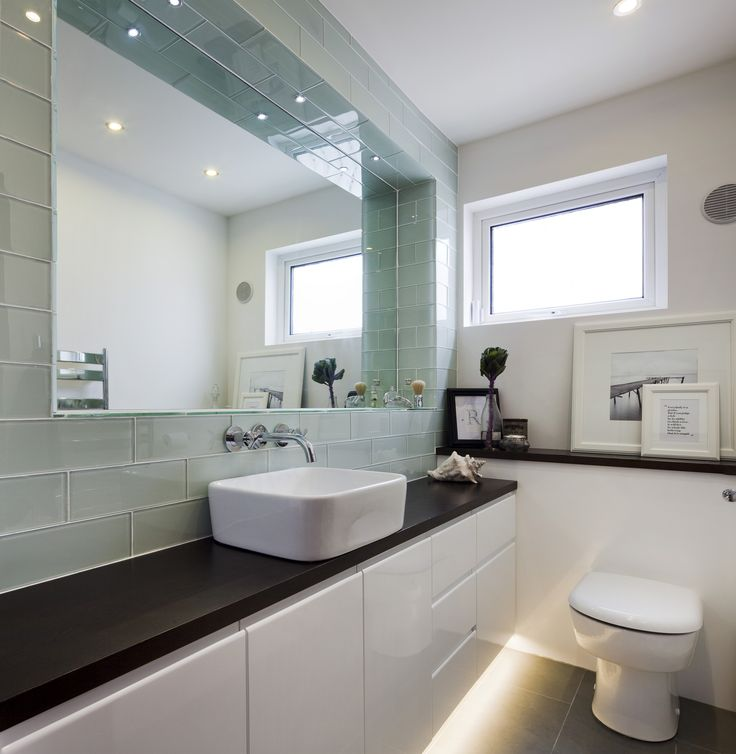 Glass rectangular tiles frame a large recessed mirror, reflecting plenty of light around this small bathroom.A bespoke high gloss storage unit with LED strip lighting creates a strong line, elongating the space. The dark stain solid oak top defines the contemporary geometric style. www.kingstonlaffertydesign.com