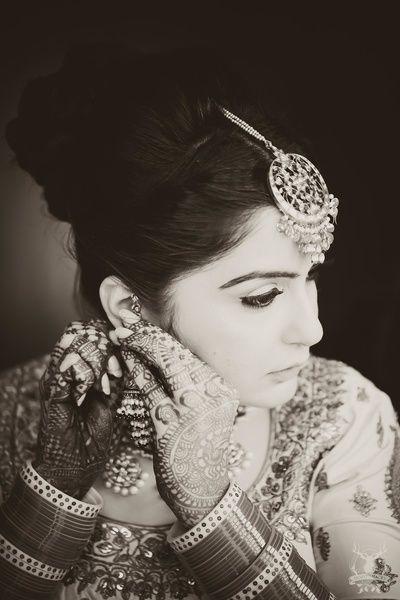 black and white bridal portrait, bride adjusting jewellery, bride adjusting earring, large maang tikka, , gold maang tikka, circular maang tikka