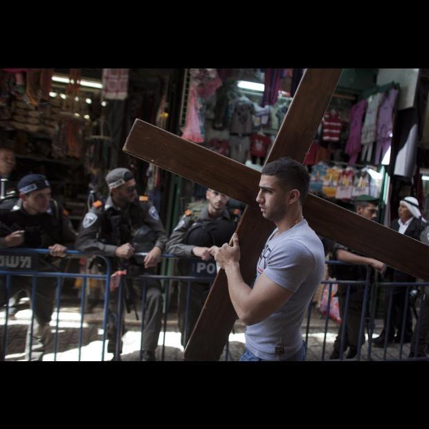 Un peregrino católico palestinos pasa junto a varios policías israelíes con una cruz al hombro durante su participación en el Vía Crucis del Viernes Santo por la Vía Dolorosa en Jerusalén (Israel) hoy, 6 de abril de 2012. Miles de peregrinos católicos, clérigos y turistas se encuentran en la ciudad para participar en las celebraciones de la Semana Santa. EFE/Oliver Weiken