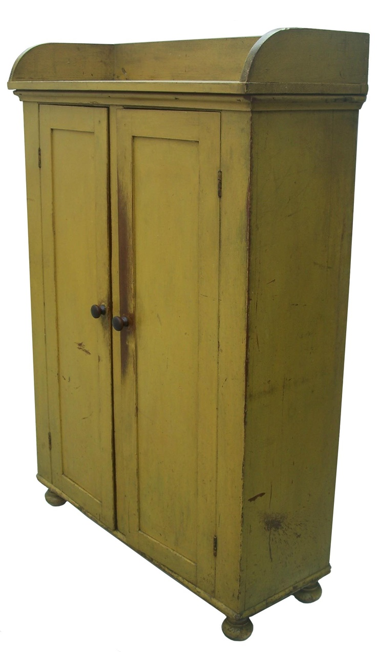 Early 19th century Buck's county Pennnslyvania tall two door Storage cupboard, with applied gallery in original bright mustard paint, with nice onion turned feet