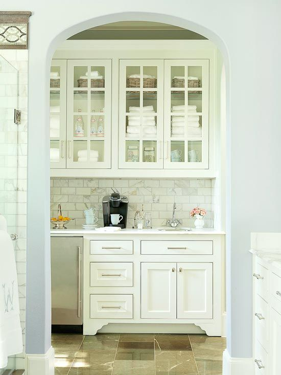 Shorten Your Steps - A kitchenette just off the bath outfitted with a sink, coffee station, mini refrigerator, and slim dishwasher easily incorporates breakfast into the routine. A generous 6-foot-long line of cabinets offers pretty and practical storage for extra bath towels and toiletries, as well as spots to stash coffee mugs, canisters of beverage supplies, and favorite late-night snacks.