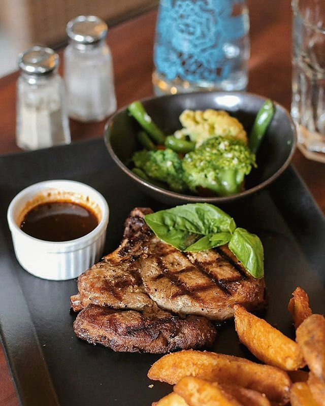 Bali Bakery's Grilled Pork Chop. Served with olive rice or potato wedges sauted vegetables and black pepper sauce.  And this is so tasty & juicy. --- @BaliBakeryOfficial #Seminyak #SeminyakSquare Bali --- #balibakeryseminyak #balibakery #grilledporkchops #blackpeppersauce #porkchops #steakdinner